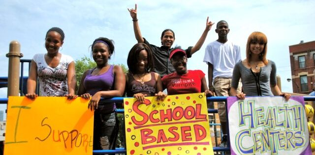 Image of Students holding signs supporting SBHCs